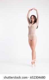 Girl brunette ballerina in beige tight suit on pointes posing on white background