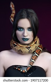 girl brunette green eyes gaze close up portrait with a snake yellow brown mottled python wrapped around her neck