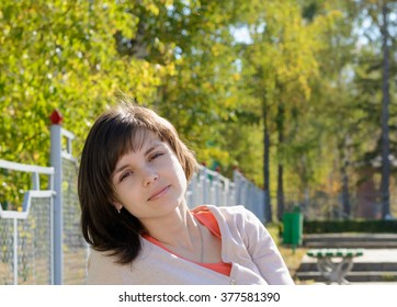 Girl brunette sitting in the park in the summer