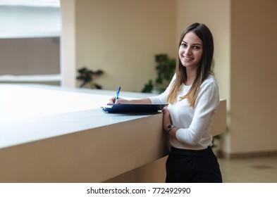 Girl brunette student writing in notebook.