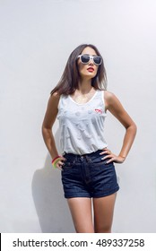Girl brunette in summer in park with resting in shorts and a white blouse on a white background fashion lifestyle, gentle look. Sensual make-up, tanned skin and bright red lipstick. In sun glasses.