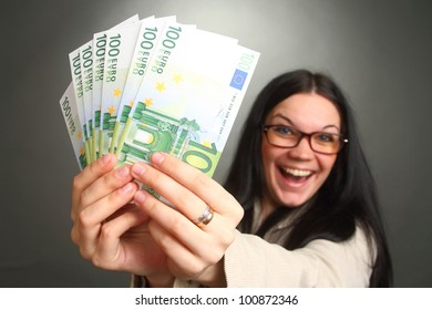 the girl the brunette wearing spectacles holds a lot of money, looks in the chamber