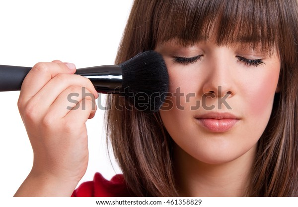 girl with brush and closed eyes makes makeup