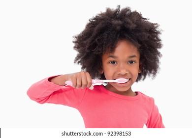 Girl brushing her teeth against a white background