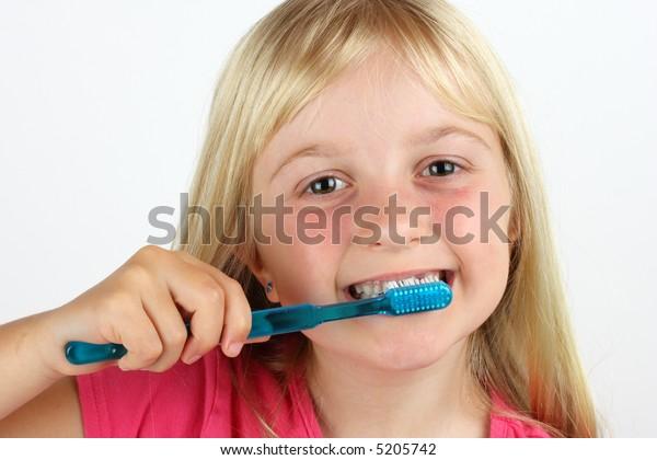 Girl brushing her teeth against white background