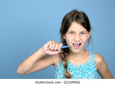 Girl brushing teeth against a blue background, leaving room for typing. Photo was taken in september 2014.