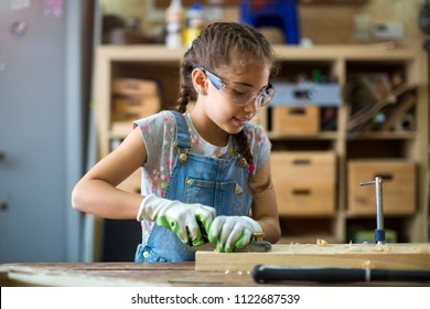 Girl building birdhouse in garage