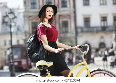 Girl in burgundy shirt, black skirt and hat with bag riding a bicycle, looking at camera and smiling. Cycling, city, outdoor