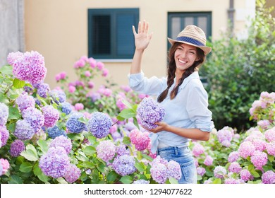 Girl is in bushes of hydrangea flowers in blooming garden. Young woman greets neighbors or welcomes guests and visitors. Concept of countryside life style, gardening, hospitality.