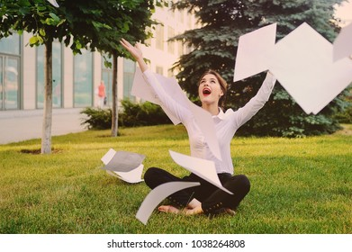 Girl in business office clothes sitting on grass throwing office documents or white sheets of paper