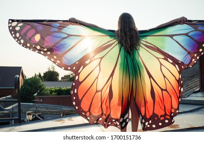 A girl in a butterfly costume is dancing on the roof. She is sunny and funny.