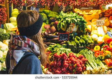 Girl buying fruits and vegetables at the marketplace