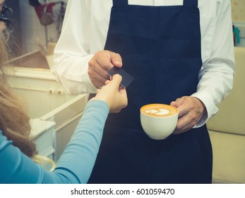 The girl buys coffee with a credit card.