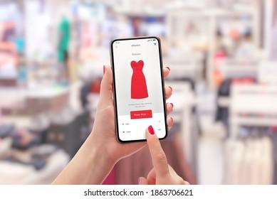 Mädchen kauft ein rotes Kleid mit Smartphone online. Bekleidungsgeschäft im Hintergrund