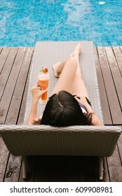 Girl  by the pool with drink