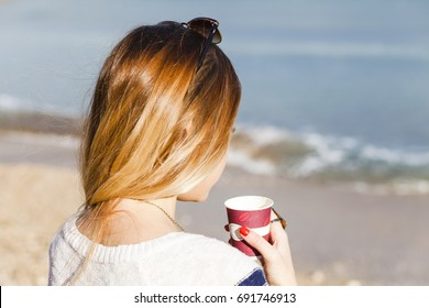 girl by the sea drinking a tea warm filter applied