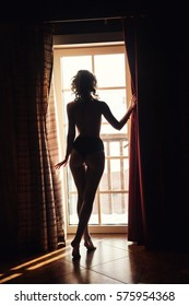 The girl is by the window. The girl has opened curtains and looks out of the window