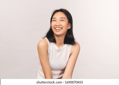 Girl cackles and looks up at empty space for text and your ad. Beautiful young woman Asian appearance with black hair brown eyes stands isolated white background in Studio