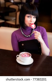 girl in cafe with coffee eat lollipop