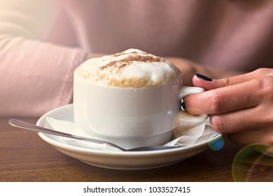 Girl in a cafe with a cup of cappuccino. Female hands holding a cup of coffee - cappuccino.