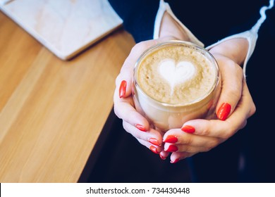 A girl in cafe with red nails is holding a cup with cappuccino with a pattern in the form of a heart