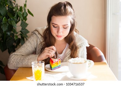 A girl in a cafe sits near a window and eats a bright piece of cake and drinks cocoa with a marshmelow from a huge mug. The girl is bathed in sunlight from the window.