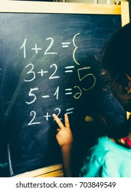 Girl calculating by fingers to write the answer on chalkboard
