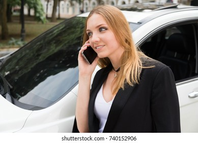 The girl is calling by the phone near the car