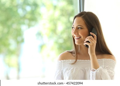 Girl calling on phone land line and looking outdoors through a window in the living room at home