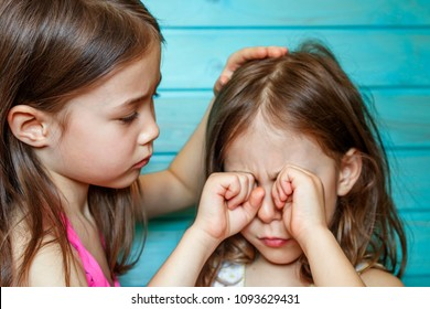 The girl calms her crying friend. Children's friendship, support