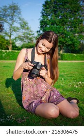 Girl with the camera in the park smiling and looking happy