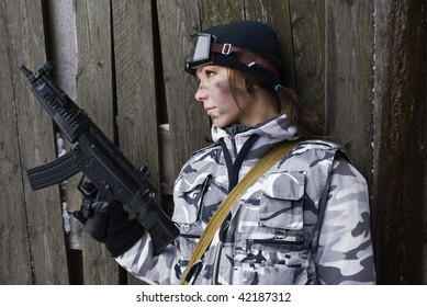 Girl in a camouflage with the gun in hands