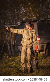 Girl in camouflage with hunting dog