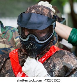 girl in camouflage and protective mask before playing paintball