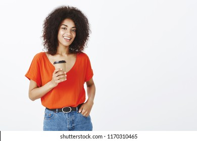 Girl can deal with any task. Confident good-looking african-american female student with afro haircut, holding cup of coffee and hand in pocket, smiling friendly, being self-assured over gray wall