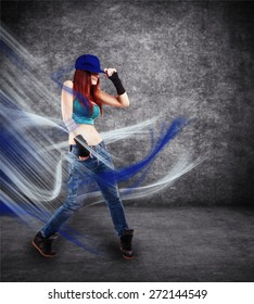 girl in a cap, jeans, t-shirt and sneakers dancing on a gray background