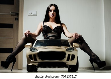 Girl in car toy. escort and sexual services. Driver girl sit in car. Beauty and fashion. Woman in black lingerie and shoes.