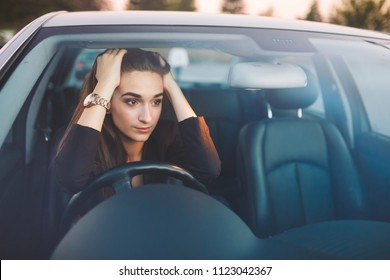 The girl in the car is in a traffic jam.