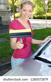 Girl at car wash cleans windshield with cleaner and wiper puller on a sunny day