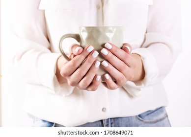 Girl in cardigan holding a cup of coffee. Close-up.