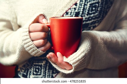 Girl in cardigan holding a cup of coffee. Close-up