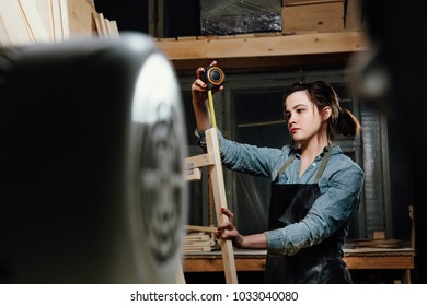Girl carpenter with a tape measure on a background of wooden pieces in workshop. working conducts measurements. Woman in apron.