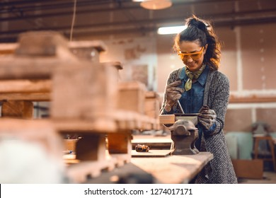 Girl in carpentry workshop doing wood job with protective glasses on.