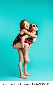 Girl carrying her friend on her back. Small girl in swimwear giving her friend piggyback ride on blue background.