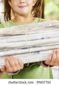 girl carrying newspapers for recycling, cropped view