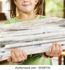 girl carrying newspapers for recycling, looking at camera