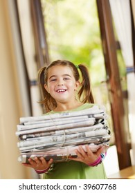 girl carrying newspapers for recycling, looking at camera, copy space