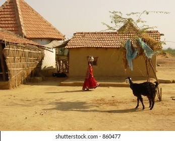 a girl carrying a vessel on her head in a village in india