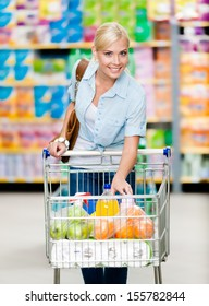 Girl with cart full of food in the shopping center. Concept of consumerism, retail and purchase