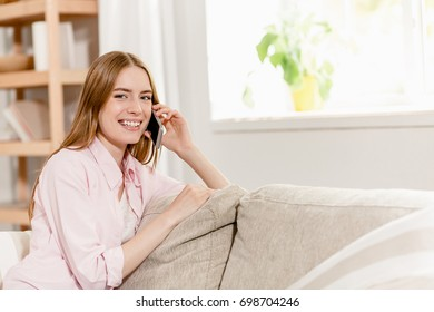 Girl in casual clothes making call with smartphone sitting on sofa. Woman relaxing at home calling her friend.